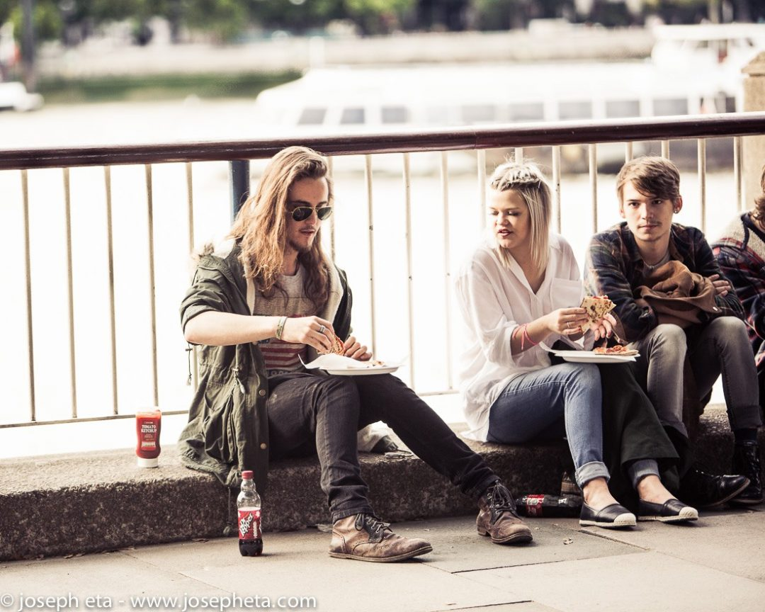 Three friends sharing a pizza at the South Bank in London