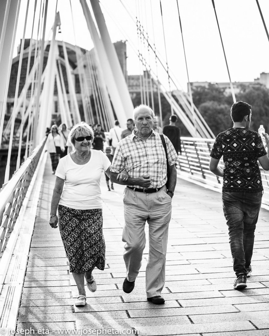 A mature couple walking on the Hungerford bridge at the South Bank in London