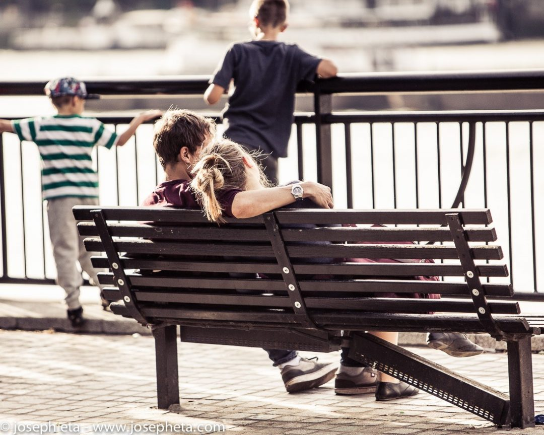 A couple sitting on a bench at the South Bank in London and watching the sunset
