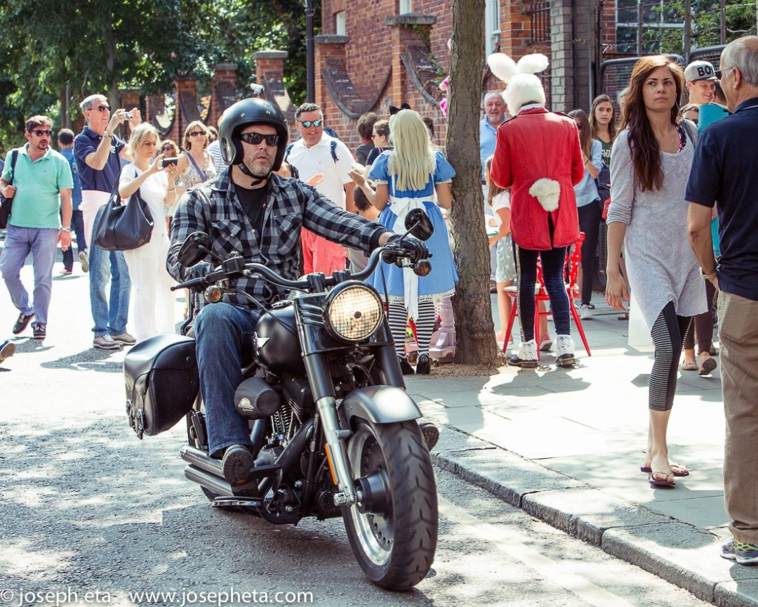 A man riding his harley davidson bike through the portobello road market