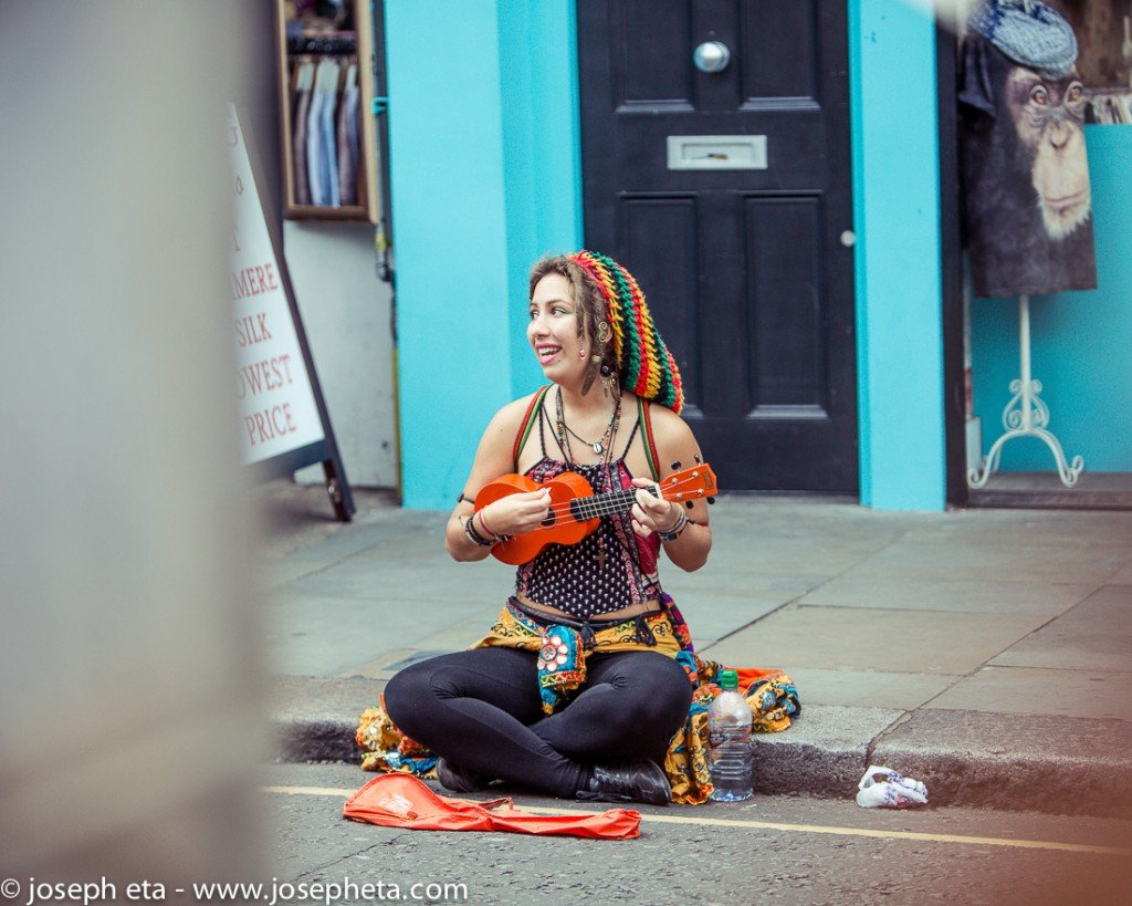 street photopgraphy of a woman playing her ukelele at portobello road in London