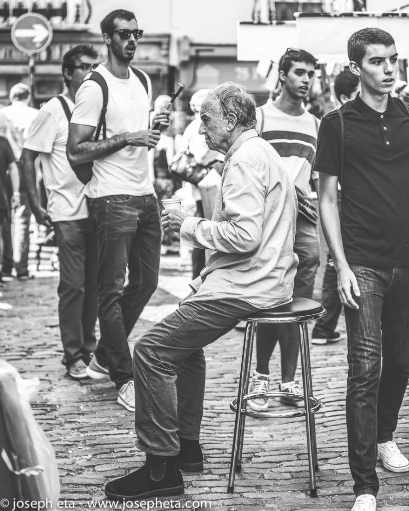 street photography of an elderly man sitting on a stool at portobello road market in London