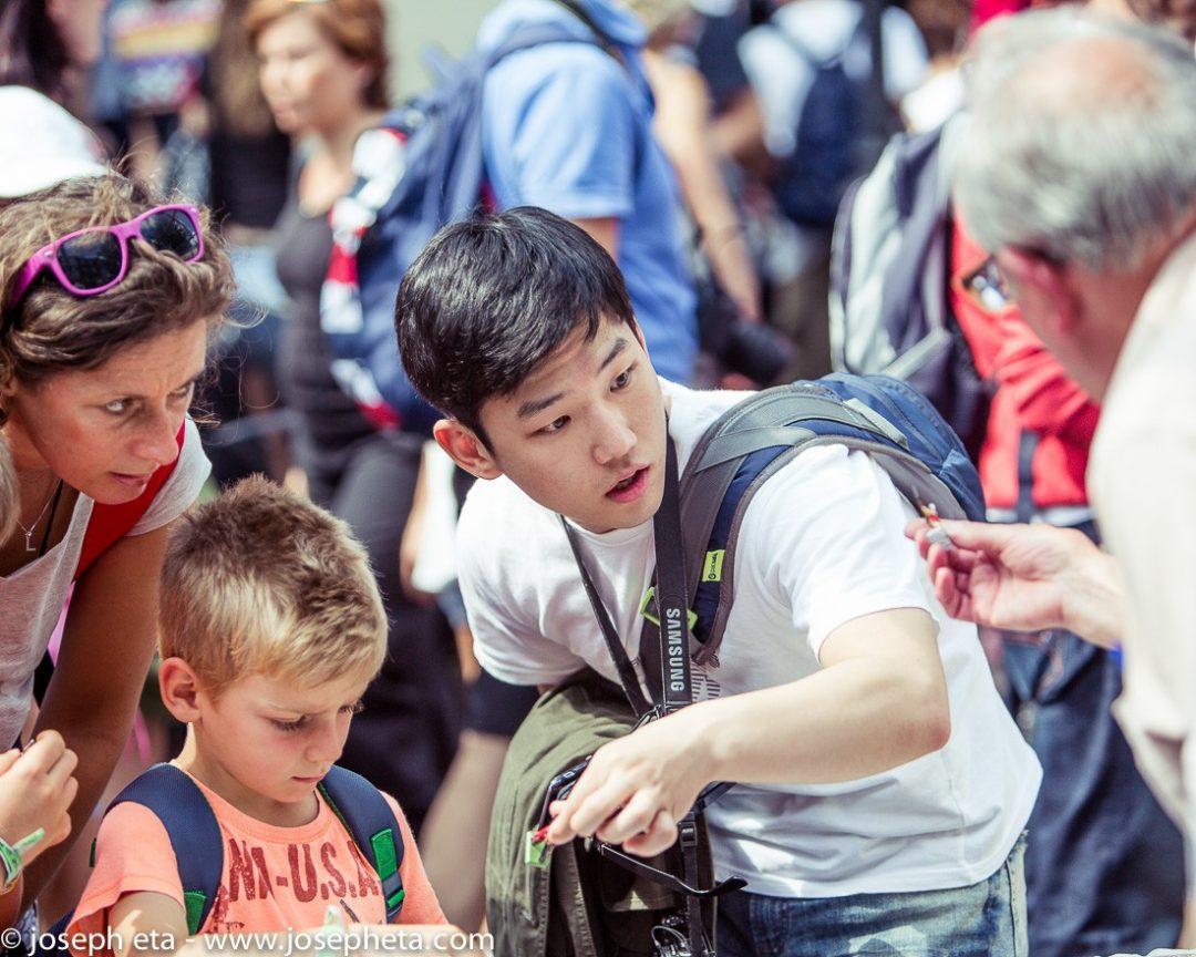A Japanese tourist inspecting a miniature model figure at London portobello road market