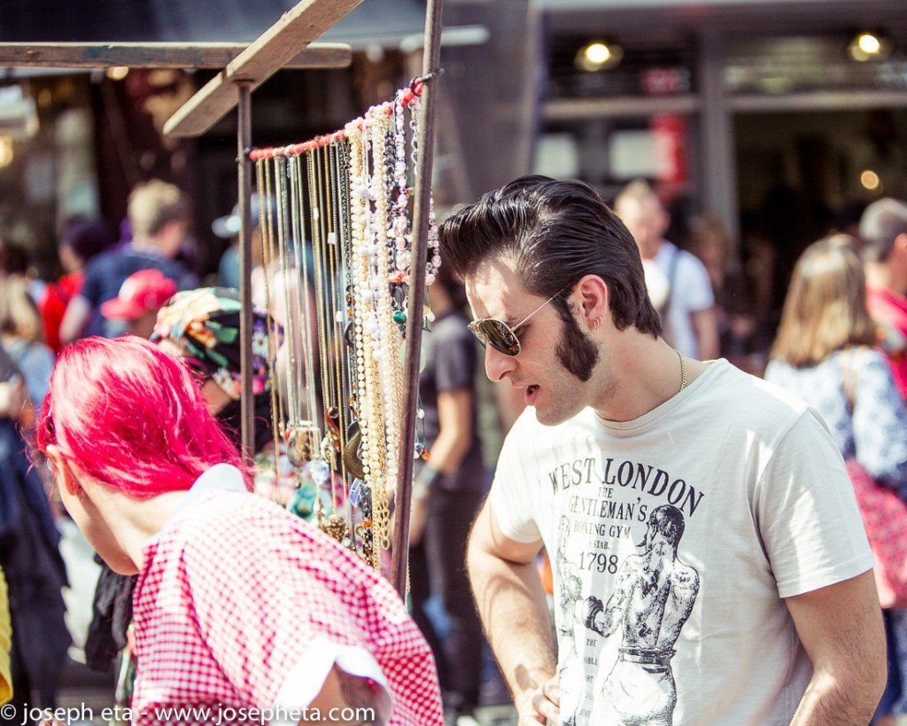 street photography of an Elvis Presley look-alike with his pink haired girlfriend browsing jewellery at London portobello road market