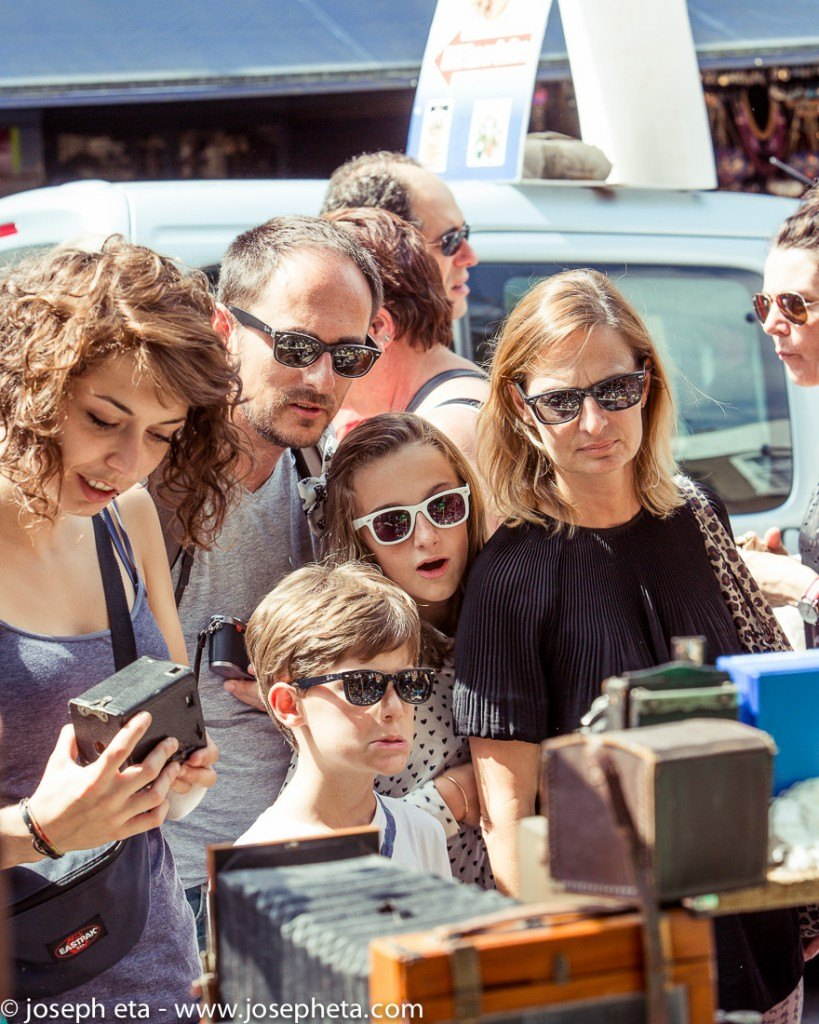 Street photography of a family of 4 browsing antique cameras at London Portobello Road market