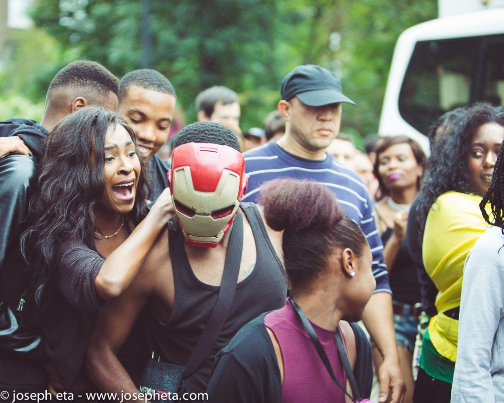 street photography of a man in an iron man mask dancing between two women at the London Notting Hill Carnival