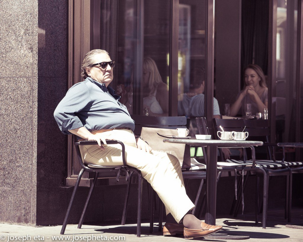 An elderly man having coffee in a cafe in Piccadilly in London