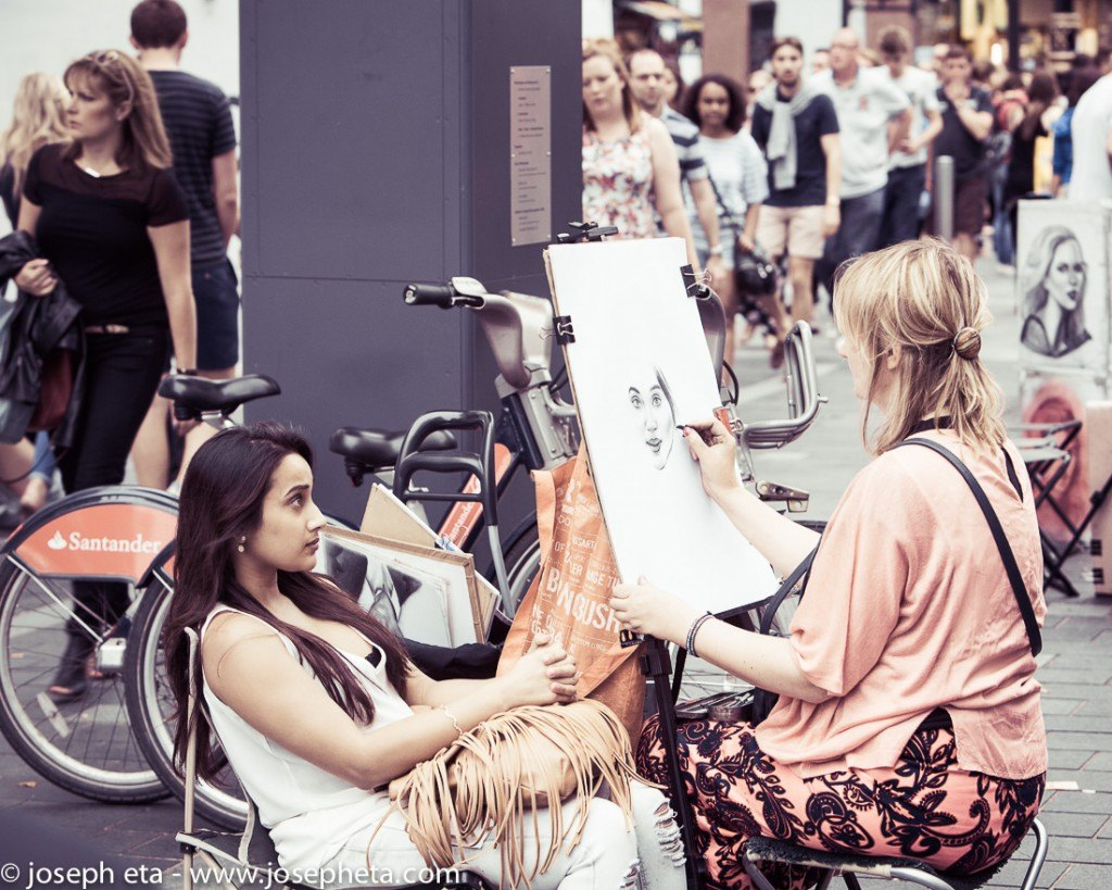 An artist painting the portrait of a young woman at Leicester Quare in Piccadilly in London