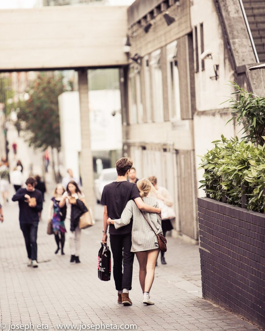 A couple walking with their shopping bags along the South Bank in London