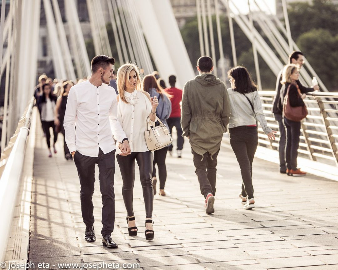 A couple walking hand in hand across the Hungerford Bridge on the South Bank