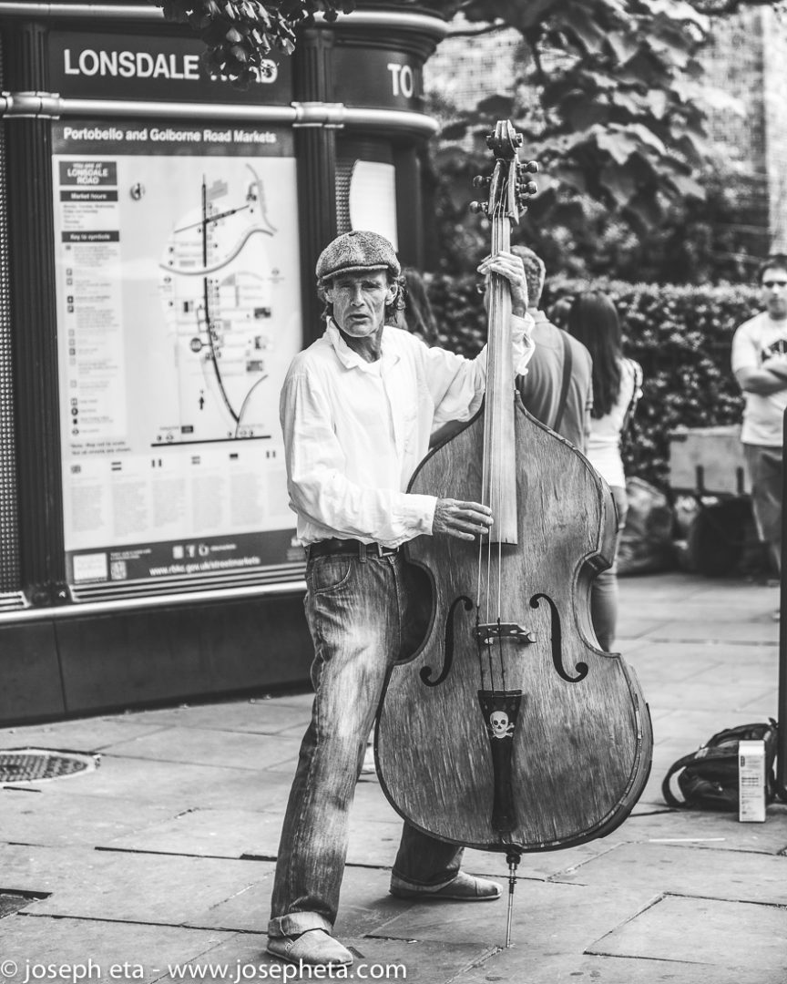 a street performer playing a bass guitar at portobello road market
