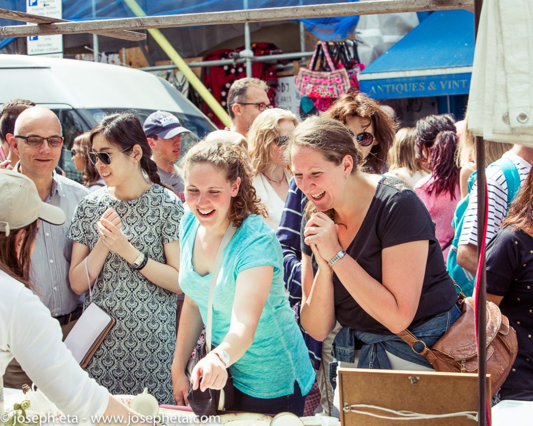 Two women giggling after finding a precious antique item at London Portobello Road Market