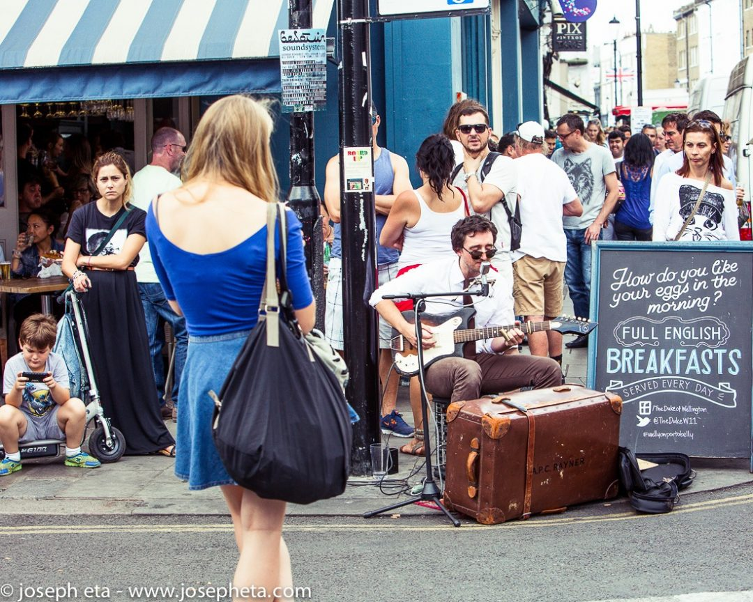 A street musician playing a guitar on the pavement at London portobello road market