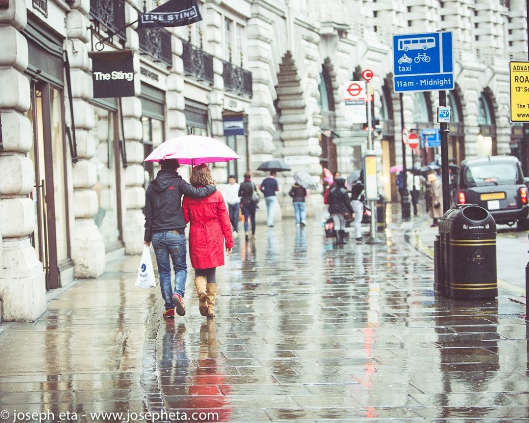 A couple walking down Regents Street in the rain in London
