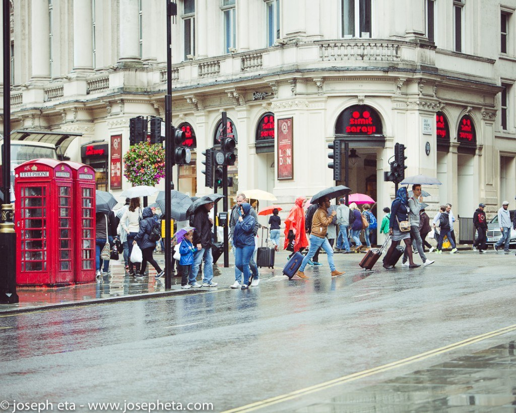 street photography of travellers in the rain crossing the road at Piccadilly circus in London