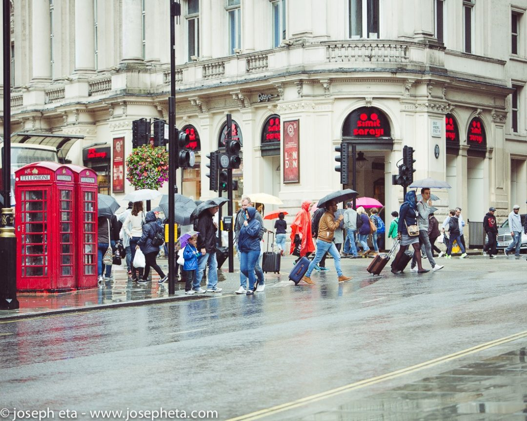 travellers in the rain crossing the road at Piccadilly circus