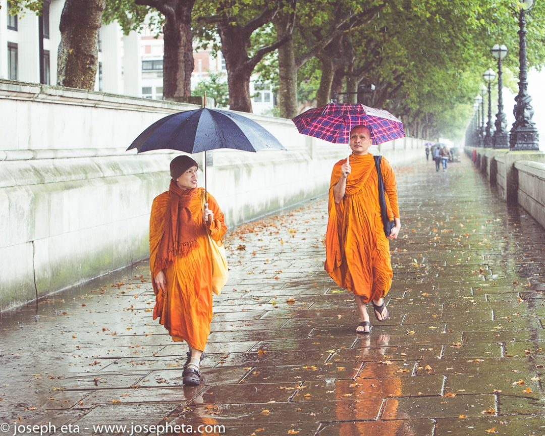 Two monks walking in the rain towards Westminster bridge