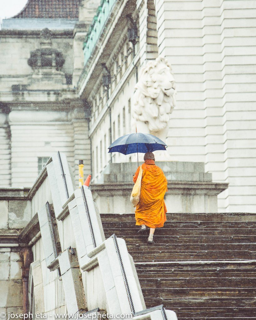 A monk in London rainfall climbing stairs on the South Bank