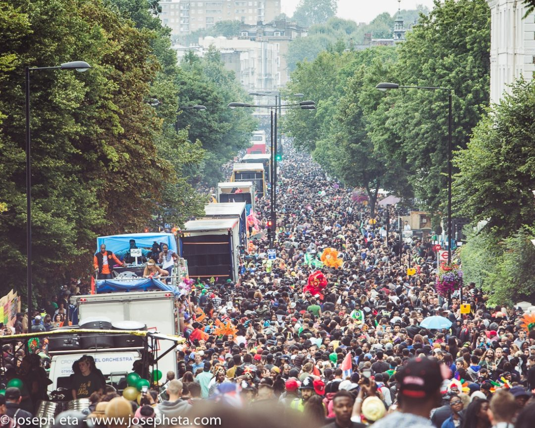 photo of huge crowds and carnival bands and trucks going by at the Notting Hill Carnival in London