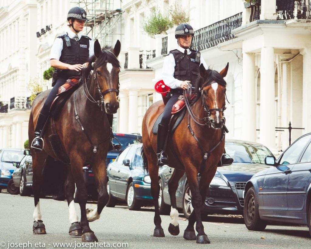 street photograohy of a photo of a policeman and a policewoman on horseback during the Notting Hill Carnival in London