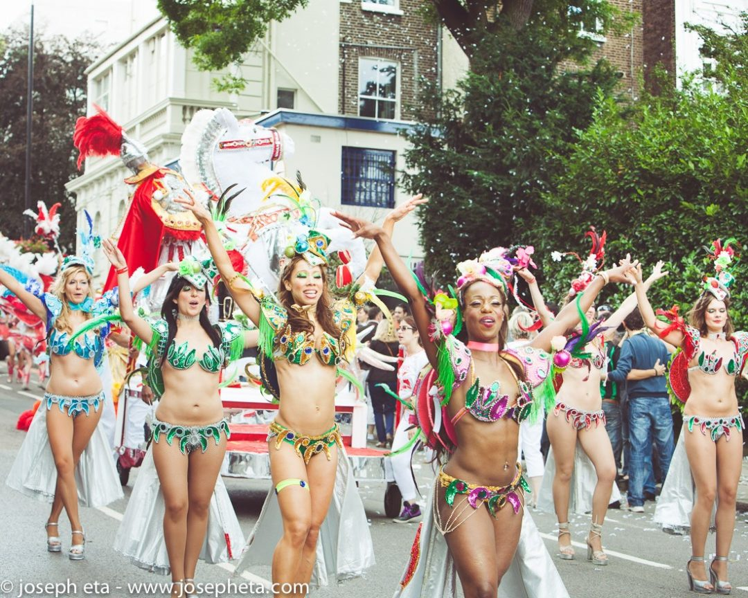 photo of colourful carnival dancers on a parade at the Notting Hill Carnival in London