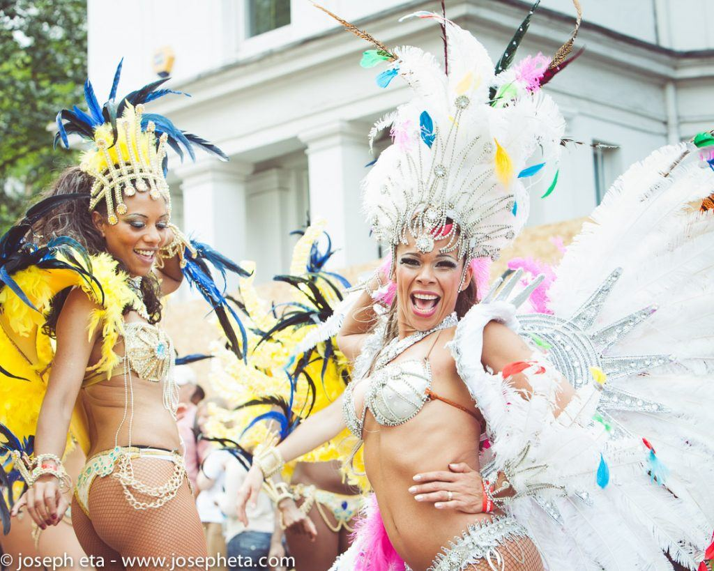 street photography of two carnival dancers dancing samba at the London Notting Hill Carnival