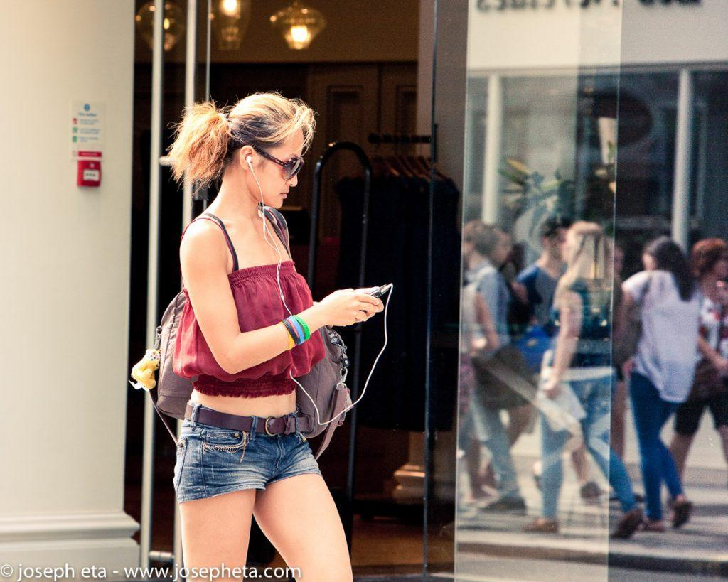street photography of a lady walking and focused on her phone in Covent Garden in London