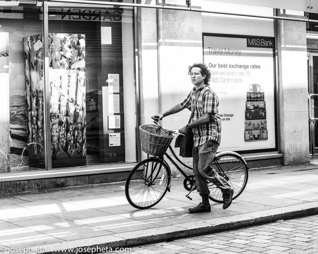 Street photography of a man pushing his bicycle in Covent Garden in London