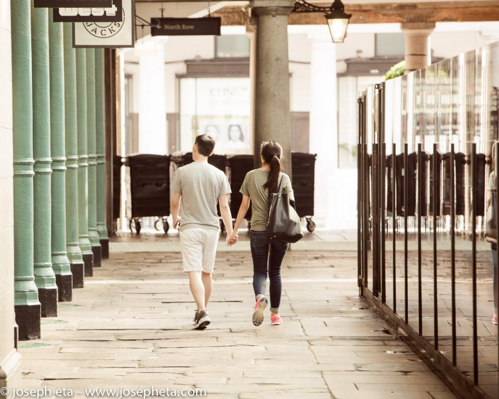 Street photography of a couple walking hand in hand across the open piazza in Covent Garden in London