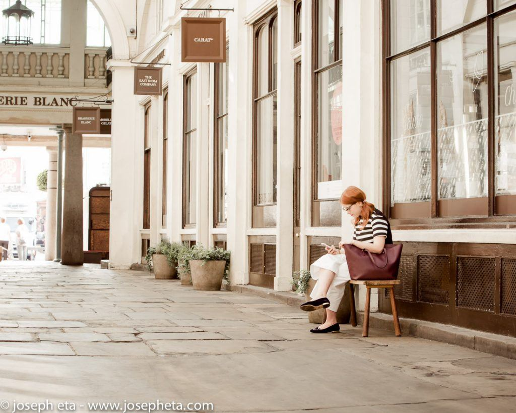Street photography of lady sitting on a public bench in an alley way in Covent Garden in London