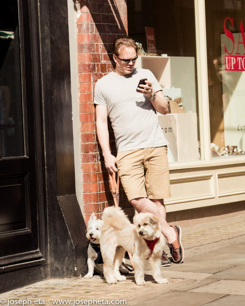 Street photography of a man walking his two dogs in Covent Garden in London