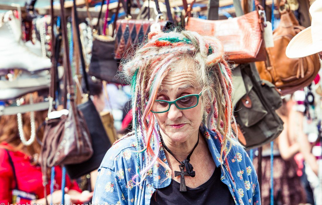 A trader with multi colored dredlocks at the London portobello road market