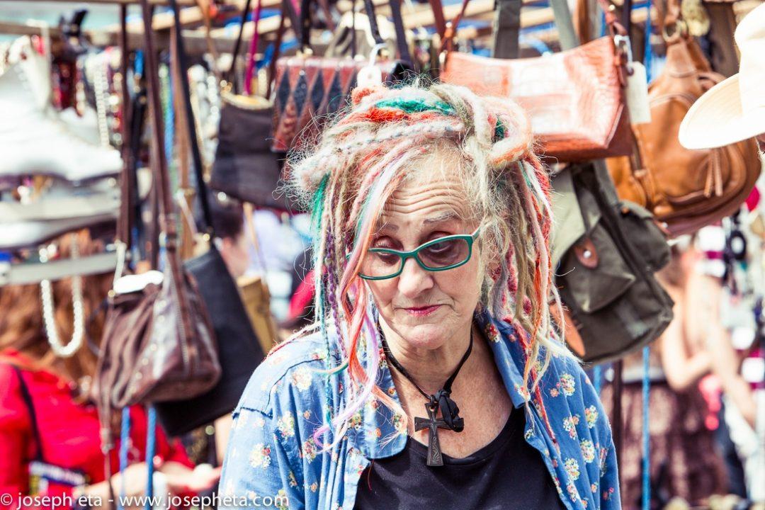 A trader with multi colored dredlocks at the London portobello road market
