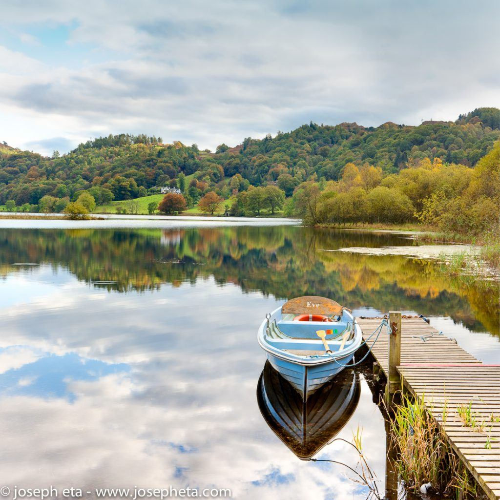 A boat at a jetty on lake Grassmere in the Lake District in the UK