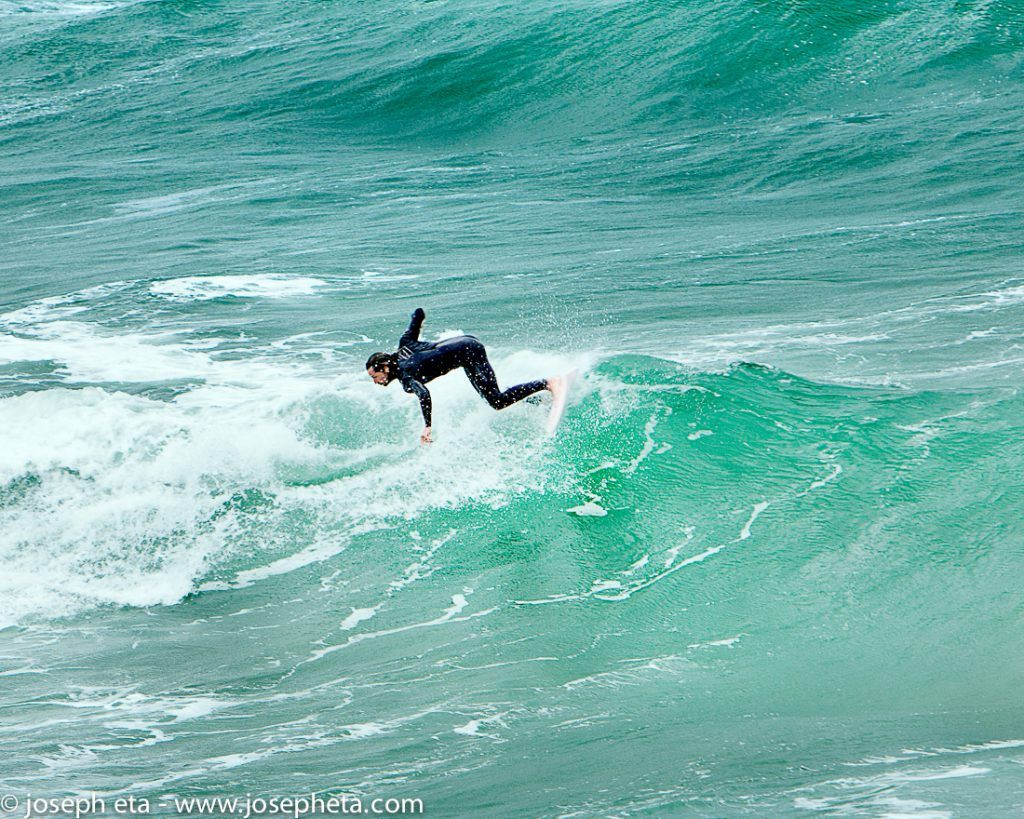 Photo of a man surfing a wave at Fristal beach in Newquay in Cornwall