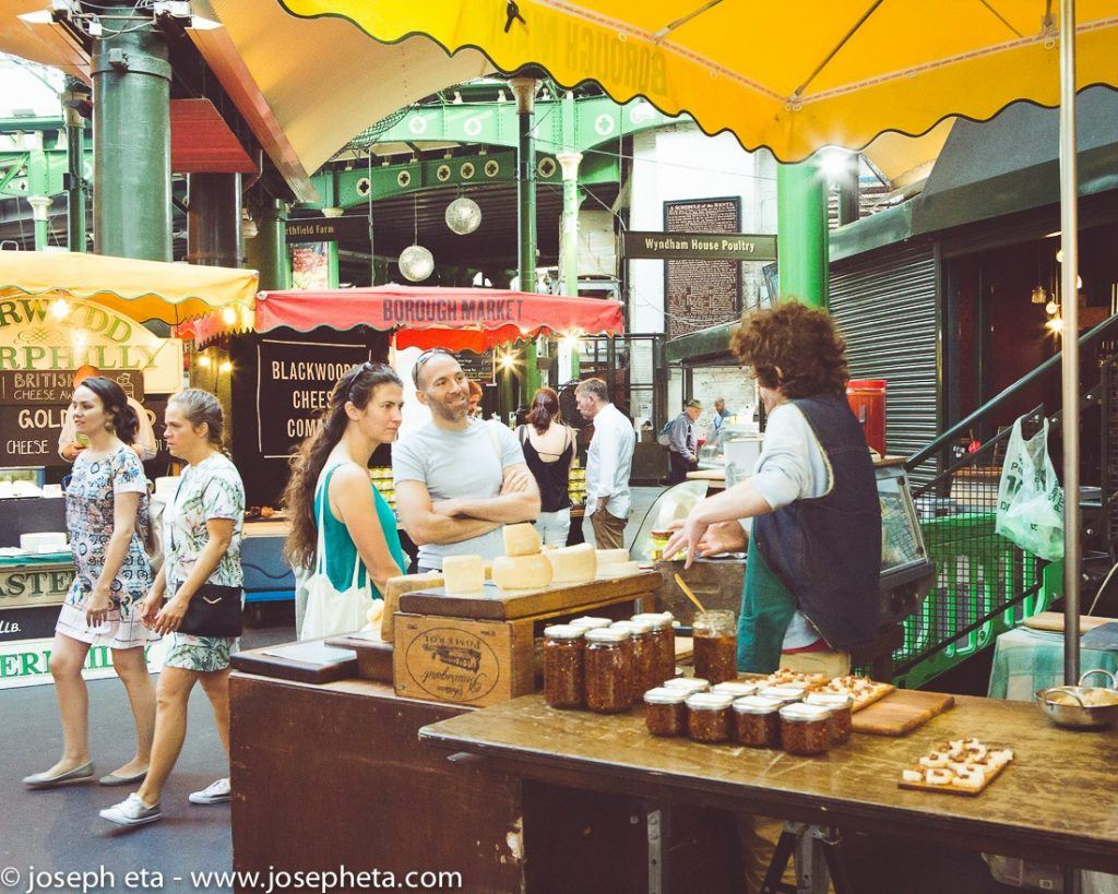 A couple of customers talking to a jam trader at London Borough market