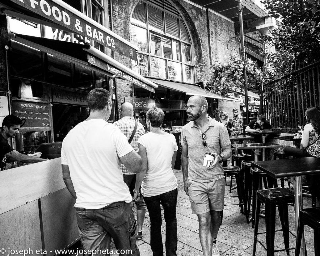 A Londoner walking past a bar at London Borough Market