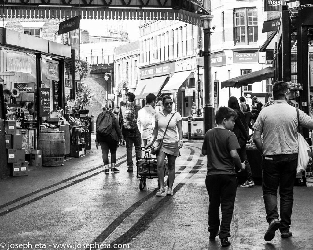A woman pushing her shopping strolley are London Borough market