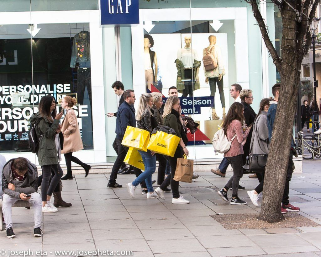 street photography of shoppers on Oxford street carrying Selfridges bags