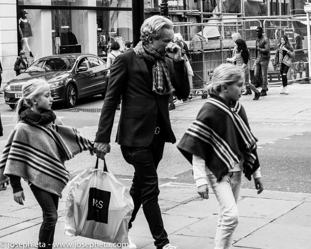 Street photography of a father shopping with his two daughters on Oxford street in London