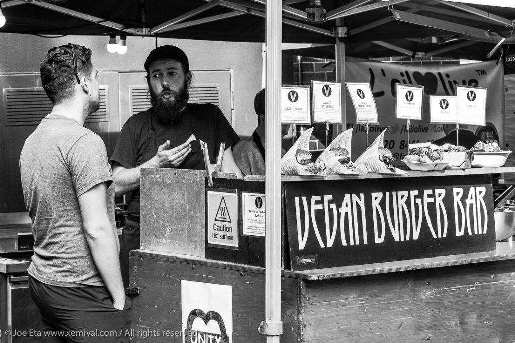 A customer buying a vegan burger at London Borough market