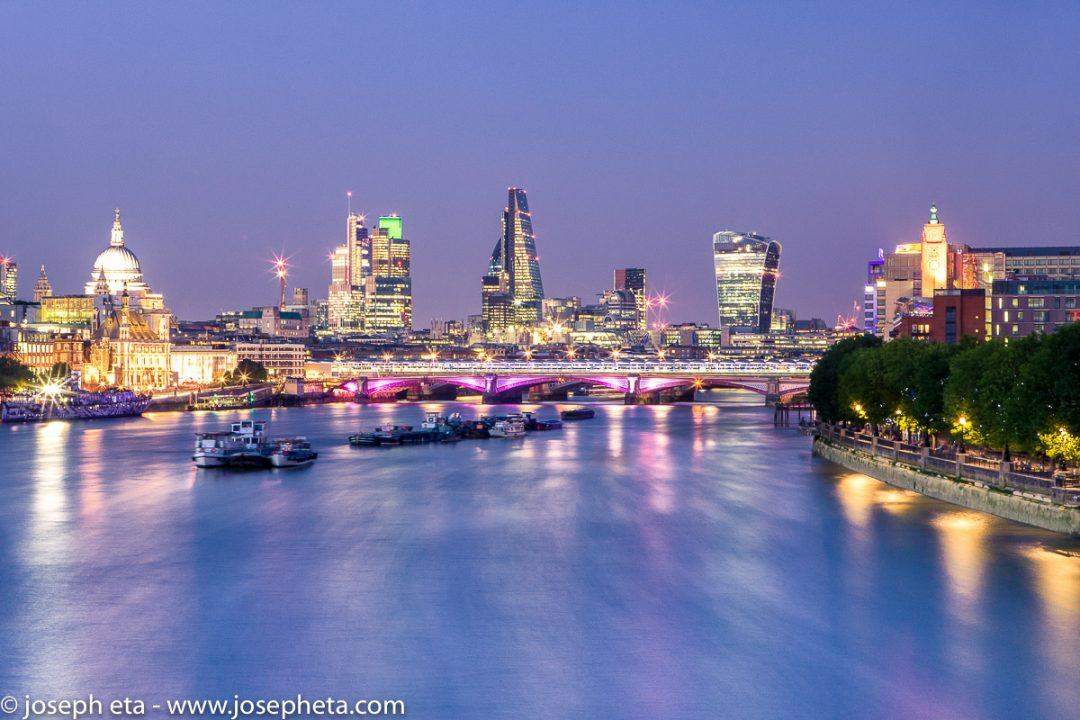 An expansive River Thames at dusk with the illuminated buildings of St Paul's Cathedral, the Shard, and the Walkie Talkie, on the skyline.